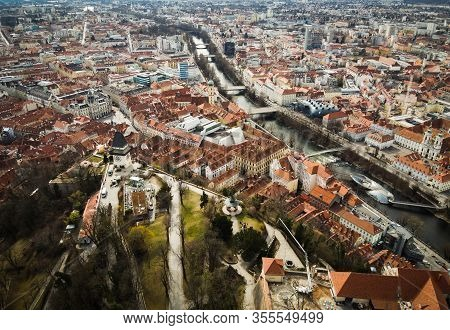 Aerial View From Graz Hill Schlossberg In Austria, Cityscape With House Roofs, Mur River And All Fam