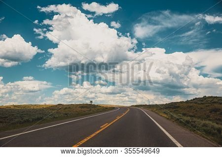 White Clouds Float Above The Horizon Over A Curving Highway With Dotted Yellow Lines. Wispy And Cumu