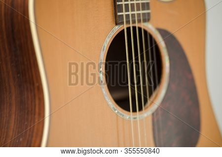 Close-up Details Of A Dreadnought-style Acoustic Guitar With Bronze Or Steel Strings. Guitar Has Int