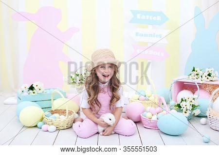 Easter Concept And Family Holiday! Little Girl Playing With Easter Bunny. Easter Colorful Decor In H