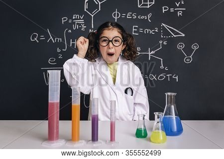 Happy Scientist Child With Glasses In Lab Coat With Chemical Flasks Celebrating An Idea, School Blac