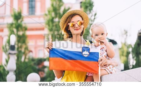 Woman With Little Child Holding Slovenian Flag On Central Square Of Ljubljana. Family Walking In Eur