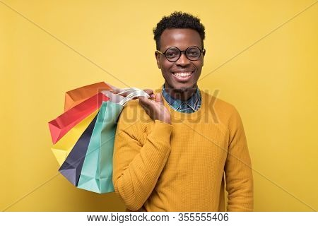 Young African American Man In Yellow Sweater And Glasses Holding Shopping Bag
