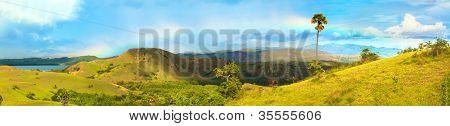 Panorama of the Rinca island. Rainbow over savanna