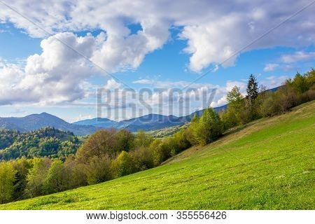 Stunning Rural Landscape In Mountains. Fields And Meadows On Hills Rolling In To The Distant Ridge.
