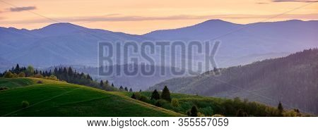 Panorama Of Mountainous Countryside In Springtime At Dusk. Trees On The Rolling Hills. Ridge In The