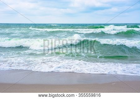 Waves Crash On Sandy Beach. Cloudy Weather Before Storm On The Sea