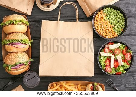 Different Tasty Food From Delivery Service On Wooden Background