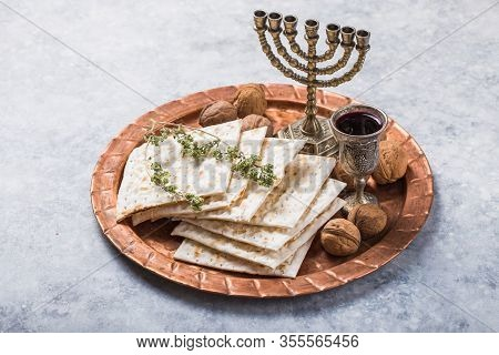Passover, The Feast Of Unleavened Bread, Matzah Bread And Red Wine Glasses On The Shinny Round Metal