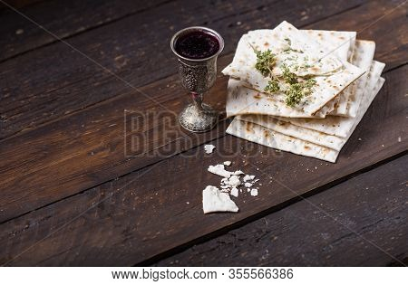 Passover. Red Kosher Wine With A White  Matzah Or Matza On A Vintage Wood Background Presented As A