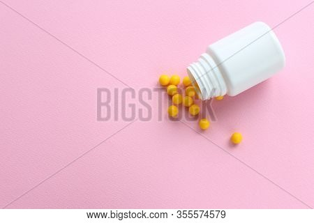 Yellow Vitamins Scattered On A Pink Background