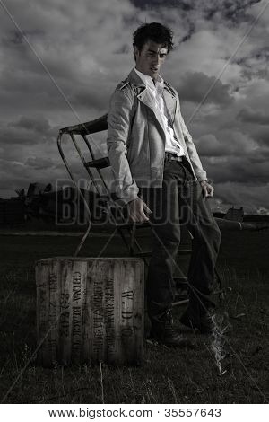 Dark moody image of a young man in a casual jacket standing alongside a vintage crate under a threatening stormy sky