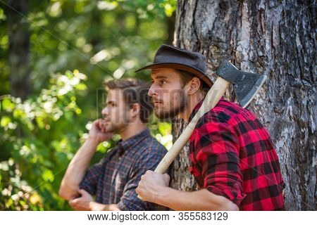 Lumberjack With Chainsaw And Ax. Harvest Firewood. Hiking In Deep Wood. Forest Care At Vacation. Sum