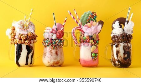 Different Delicious Freak Shakes On Color Background