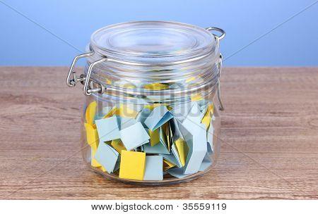 Pedazos de papel para la lotería en el vaso de la mesa de madera sobre fondo azul