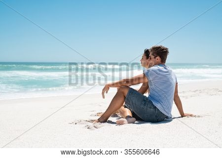 Young couple sitting on sand by sea looking at the horizon and thinking about the future. Happy man and beauty woman enjoying vacation. Thoughtful couple on beach contemplating the ocean, copy space.