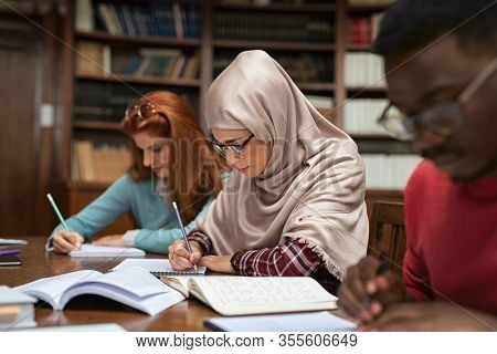Focused student in hijab studying with classmates in university library. Islamic young woman in spectacles wearing abaya and writing in notebook. Arabian girl studying with multiethnic students.