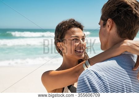 Happy young couple hugging at the beach with copy space. Beautiful latin woman embracing man while looking at him at sea. Hugging young couple standing on beach and looking at each other.