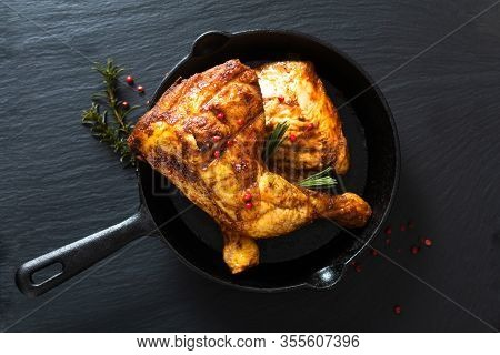 Food Concept Organic Roasted Or Grilled Chicken Leg Quarters In Skillet Iron Pan On Black Slate Ston