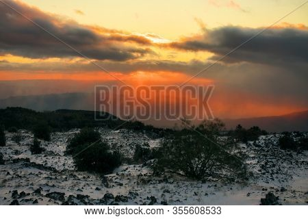 dramatic sunset on volcanic rock with snow in Etna Park, Sicily