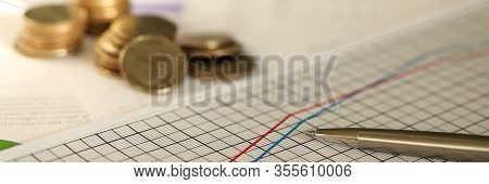 Close-up Of Valuable Metallic Currency Lying On Pile Of Important Charts Used To Investigate Success