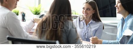 Portrait Of Business Team Sitting At Table And Having Biz Negotiations In Office. Smiling Partners D