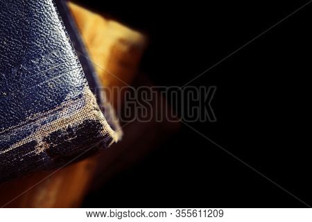 Old Book With Battered Hardcover Isolated On Black Background.