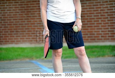Woman Holds A Pickle Ball And Paddle And Gets Ready To Serve The Ball.  She Has On Black Shorts And