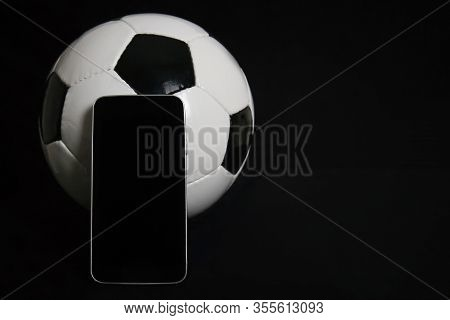 Live Football Betting Concept, Blank Smartphone Screen And Classic Football Ball Isolated On Black B