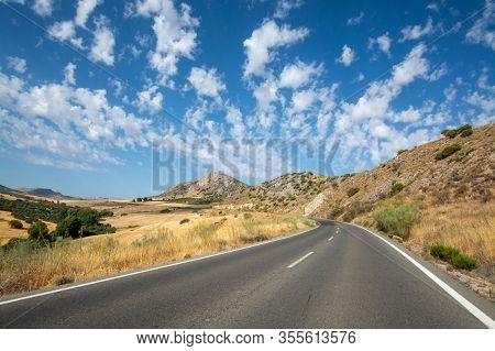 Andalusian Landscape With Yellow Hills And Blue Sky With High White Clouds