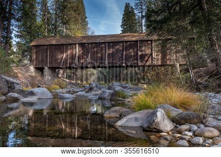 A View Of  Yosemite Wawona Covered Bridge Over The Merced  River By Mariposa, In The Fall, Featuring