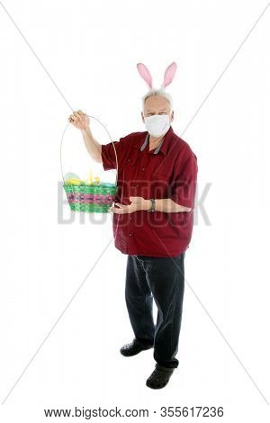 Easter Bunny. A man wears a Easter Bunny Costume and a CORONAVIRUS Paper Face Mask to Avoid Contamination and holds a Easter Basket of Treats. Isolated on white. Room for text. Clipping Path.