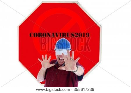 Stop Sign. Stop Coronavirus19. A man wearing a Construction Hat holds his hands out in a STOP Symbol and Screams to End COVID-19. Stop the COVID-19 Pandemic. Coronavirus19 is scaring people.