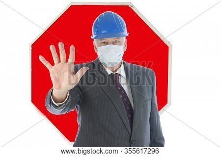 Stop Sign. Stop Coronavirus19. A man wearing a Construction Hat, Face Mask and Suit holds his hand out in a STOP Symbol. Stop the COVID-19 Pandemic. Coronavirus19 is scaring people.