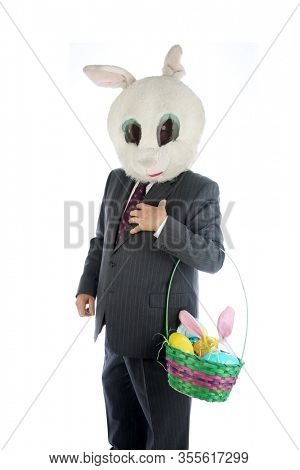 Easter Bunny. Happy Easter Bunny Man holds a gift basket of Easter Treats. Isolated on white. Room for text. Happy Easter to everyone. Clipping Path. Business Suit Bunny Man with Gift Basket.