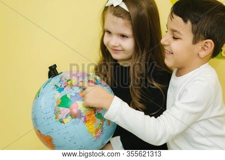 Boy With Two Girls Look At The Globe And Search Different Continets And Coutries
