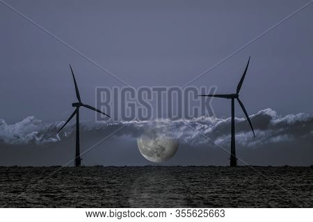 Nighttime Electricity Generation. Offshore Wind Turbines With Moon At Night Representing 24hr Clean