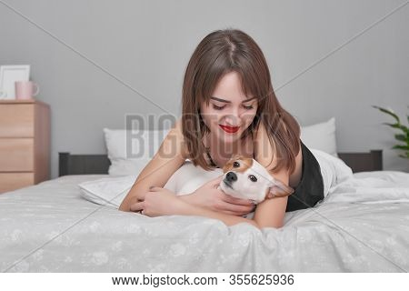 Girl And Dog In Bed. Beautiful Woman In Pajamas Sits On Bed In Bedroom With Dog Jack Russell Terrier