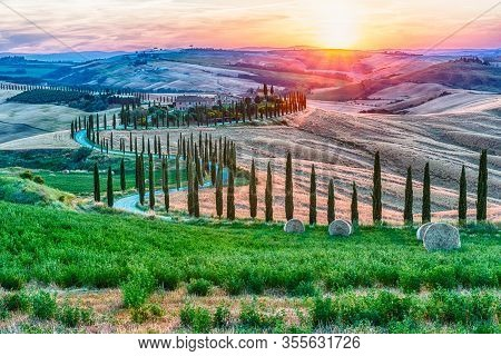 Asciano, Italy - June 23: Scenic Sunset Over One Of The Most Iconic Landscapes With Cypresses In Tus