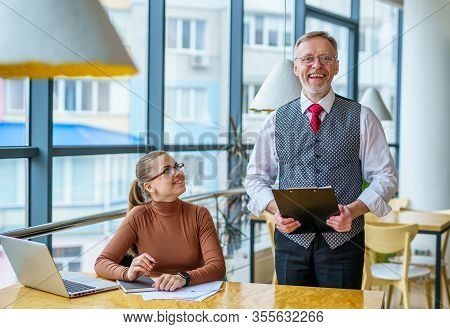 Senior Businessman Discussing Business Ideas With The Assistance. Mature Man And Businesswoman In An