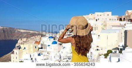 Holidays In Santorini. Back View Of Beautiful Girl Visiting Oia Village On Santorini Island On Summe