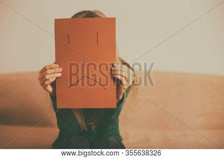 Depressed Woman Sitting Alone At Sofa And Holding Paper With Sad Face.