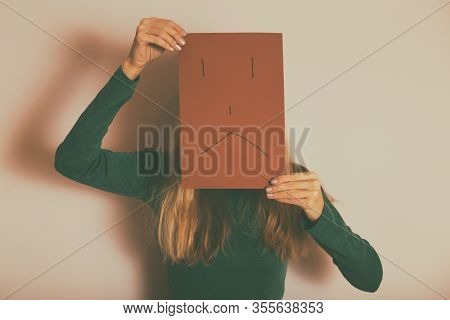 Depressed Woman With Sad Face On Paper Standing Alone In Front Of Wall.