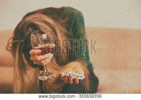 Depressed Woman Drinking Alcohol And  Pills While Sitting Alone At Sofa.