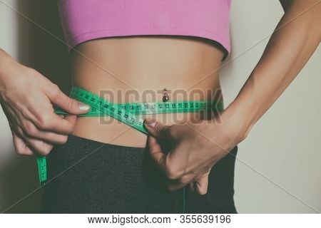 Fit Woman Measuring Her Thin Waist With A Tape Measure.