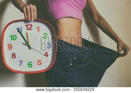 Woman In Large Jeans Holding Clock.weight Loss Concept.