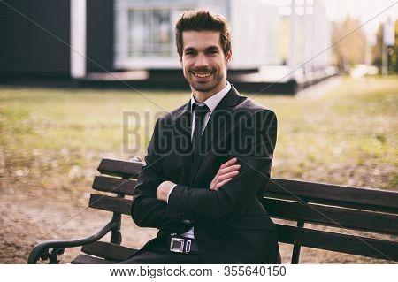Portrait Of Elegant Businessman Enjoys Sitting Outdoor