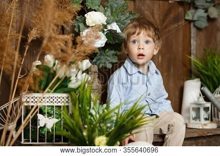 Glorious Child Playing With Easter Bunny In A Green Grass. Rustic Decoration. Studio Shot On A Woode