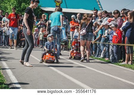 Zarinsk, Russia-june 03, 2017: Little Children Ride A Bike. Children Ride Scooters And Children's Ca