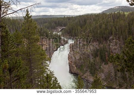 The Upper Falls Of The Yellowstone River With Unidentifiable Tourist On An Overlook And The South Ri